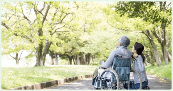 車椅子で外出している老人と女性